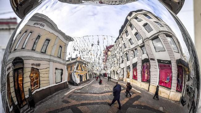 Refleksi para pejalan kaku terlihat dari ornamen dekorasi Tahun Baru di pusat Moskow, Rusia. (AFP/Yuri Kadobnov)