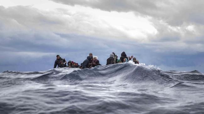 Beberapa orang asal Maroko dan Bangladesh berdesakan di perahu kayu, sementara anggota LSM Open Arms dari Spanyol mendekati mereka saat mengapung di Laut Mediterania, di lepas pantai Libya. (AP/Santi Palacios)
