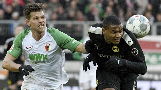 Pemain Augsburg Florian Niederlechner (kiri) berduel dengan pemain Dortmund Manuel Akanji. Dortmund tertinggal 0-2 hingga menit ke-46. (Tom Weller/dpa via AP)