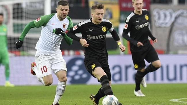 Kapten Borussia Dortmund Marco Reus berduel dengan Daniel Baier. Dortmund sempat memperkecil kedudukan menjadi 2-1 lewat Julian Brandt pada menit ke-59. (THOMAS KIENZLE / AFP)