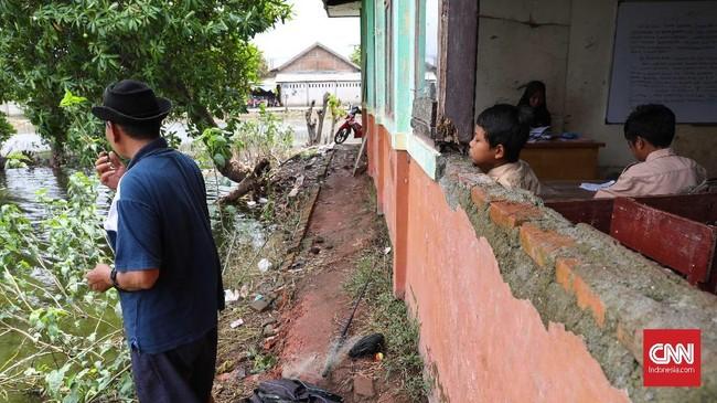 Sesekali murid menengok ke arah luar jendela yang bolong tak memiliki kaca. (CNNIndonesia/Safir Makki)