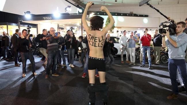 Seorang aktivis bertelanjang dada dengan tulisan