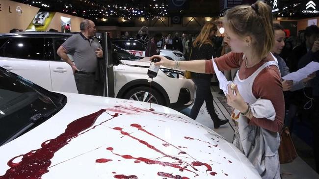 Pendemo menuangkan cara warna merah sebagai bentuk protes mereka kepada perusahaan otomotif. (Photo by FranÁois WALSCHAERTS / AFP)