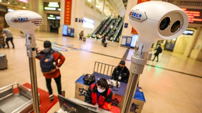 Wuhan, daerah di China yang diduga asal penyebaran virus corona tak luput memasang alat peindai suhu tubuh, salah satunya di stasiun kereta api.(Photo by STR / AFP)