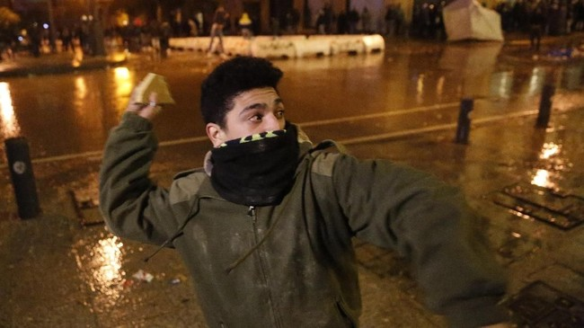 Warga Libanon melempari gedung parlemen di Beirut dengan batu sampai petasan sebagai bentuk kekecewaan terhadap komposisi kabinet baru.(AP Photo/Hussein Malla)