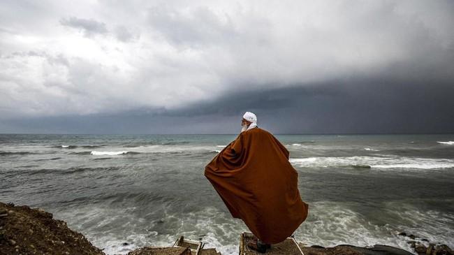Seorang pria Palestina berdiri di tengah pantai saat badai melanda rumahnya di perkampungan al-Shati di kota Gaza. (Photo by MOHAMMED ABED / AFP)