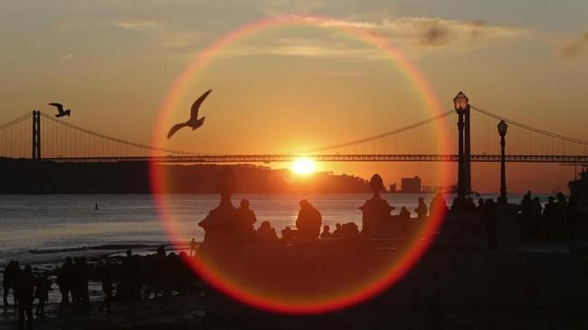 Orang-orang berdiri di pinggiran sungai Tagus sambil menyaksikan matahari yang tenggelam di Lisbon, Portugal. (AP Photo/Armando Franca)