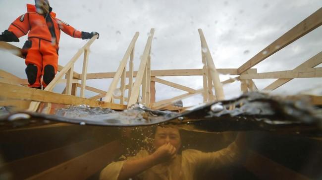 Seorang pekerja bersiaga sementara penganut Kristen Orthodox di Rusia mencelupkan diri pada sungai Neva yang membeku di St. Petersburg, Rusia. (AP Photo/Dmitri Lovetsky)