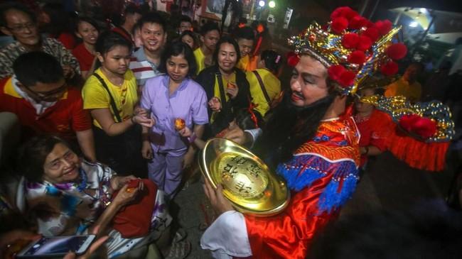 Pengurus Vihara yang berdandan ala Dewa Uang Cai Shen membagikan angpao kepada warga yang sembahyang di Vihara Boen San Bio, Pasar Baru, Kota Tangerang, Jumat (24/1). Pembagian angpao merupakan tradisi saat perayaan Imlek yang mengambil kisah cerita dari Dewa Uang Cai Shen. (ANTARA FOTO/Fauzan/ama).