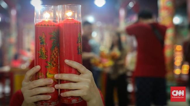 Tahapan membakar lilin sebagai doa untuk Dewa Langit agar kesehatan, rejeki dan keluarga berjalan lancar. (CNNIndonesia/Safir Makki)