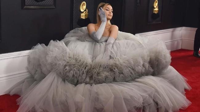 Seperti namanya, Ariana tampil 'grande' dengan ball gown abu-abu karya Giambattista Valli. Dia pun melengkapi penampilannya dengan sarung tangan berwarna senada. (Photo by Jordan Strauss/Invision/AP)