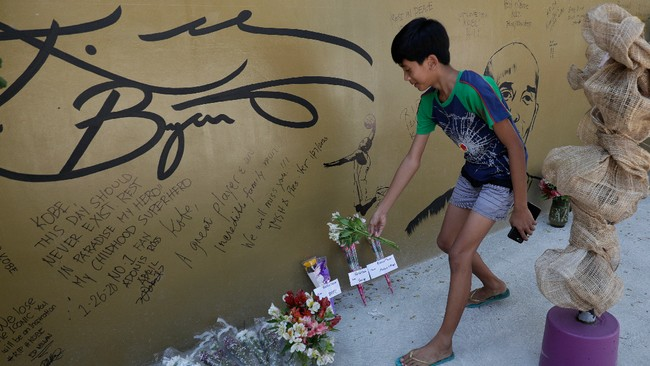 Seorang bocah menaruh bunga di depan sebuah gambar Kobe Bryant yang dipenuhi tanda tangan di 'House of Kobe' di Valenzuela, Manila, Filipina. Bryant meninggal dunia karena kecelakaan helikopter bersama tujuh penumpang lain. (AP Photo/Aaron Favila)
