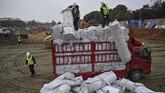 Para pekerja memindahkan bahan bangunan dari truk pengakut. (STR/AFP)