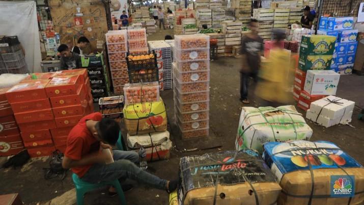 Suasana aktifitas pasar induk Kramat Jati di Blok buah, Jakarta Timur, Selasa (28/1/2020). Kementerian Pertanian  memperketat pintu masuk impor beberapa jenis makanan termasuk buah-buahan dari daerah atau negara tertentu yang kemungkinan terkontaminasi virus corona sebagai upaya pencegahan penyebaran virus tersebut. Upaya pengetatan dilakukan melalui penerapan biosecurity terhadap komoditas impor untuk mencegah penyebaran Virus Corona. Sampai saat ini, ia memastikan belum ada data yang menunjukkan kontaminasi Virus Corona terhadap komoditas impor. Pantauan CNBC dilokasi pasar pedagang pasar mengaku dagangannya normal biasa saja. Hanya saja pasoka  importir buah belum datang dan rencana april nanti. Puji salah satu pedagang mengatakan