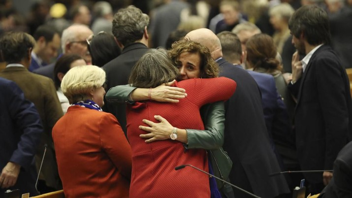 MEP's embrace after a vote on the UK's withdrawal from the EU, the final legislative step in the Brexit proceedings, during the plenary session at the European Parliament in Brussels, Wednesday, Jan. 29, 2020. The U.K. is due to leave the EU on Friday, Jan. 31, 2020, the first nation in the bloc to do so. (AP Photo/Francisco Seco, Pool)