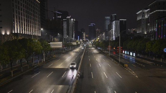 Jalanan sepi kota Wuhan di malam hari. Untuk saling menguatkan karena kota yang terisolasi, warga Wuhan dari jendela rumah dan apartemen masing-masing berteriak saling menguatkan, 'Jiayou'. Video saling menyemangati itu pun viral. (AFP/Hector RETAMAL)