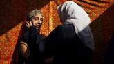 Seorang perempuan membantu model untuk persiapan sebuah pertunjukan busana di Kabul, Afghanistan pada Kamis (23/1). (AP Photo/Tamana Sarwary)