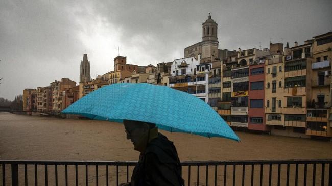 Seorang pria memegang payung saat melintasi jembatan di atas sungai Onyar ketika ada badai di Girona, Spanyol, Kamis (23/1) (AP Photo / Emilio Morenatti)