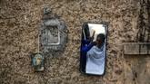 Seorang tukang cukur pinggir jalan tengah memotong rambut yang terpantul di sebuah cermin di samping gambar dewa Hindu di Kolkata, India, Sabtu, (25/1). (AP Photo / Bikas Das)