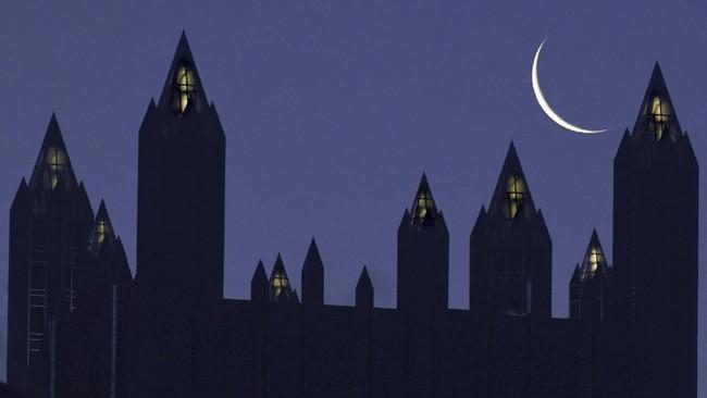 Bulan sabit tampak di langit menara PPG Place, Rabu, (22/1) di pusat kota Pittsburgh, AS. (Darrell Sapp / Pittsburgh Post-Gazette via AP)