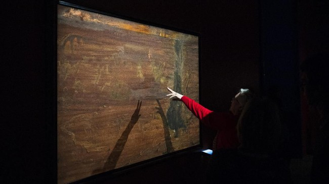 Seorang pengunjung menunjuk karya seni Salvador Dali yakni 'Raphaelesque Hallucination' di Manege Central Exhibition Hall, Russia pada Selasa (28/1). (AP Photo/Pavel Golovkin)