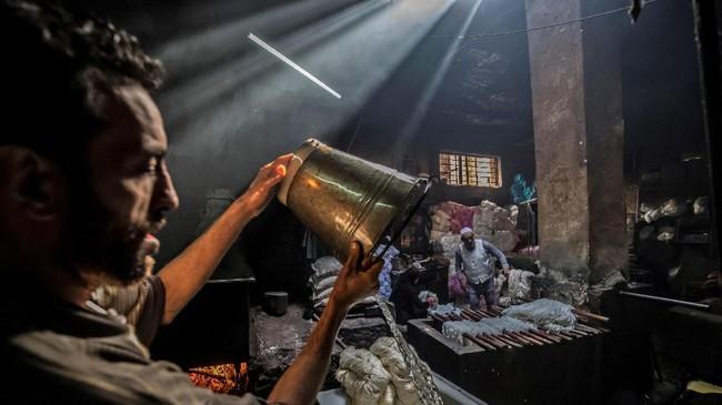 Mohamed Kamel (36) menuangkan air dari ember ke tong untuk mewarnai benang di bengkel tradisional yang sekarat di ibukota Mesir Distrik Darb al-Ahmar pada Selasa (21/1). (Khaled DESOUKI / AFP)