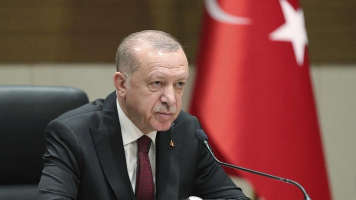 Turkish President Recep Tayyip Erdogan speaks to reporters before departing for a visit to Ukraine, in Istanbul, Monday, Feb. 3, 2020. Turkey hit targets in northern Syria, responding to shelling by Syrian government forces that killed at least four Turkish soldiers, the Turkish president said Monday. A Syrian war monitor said six Syrian troops were also killed.(Presidential Press Service via AP, Pool)