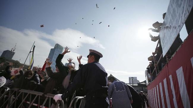 Orang banyak mencoba menangkap kacang yang dilemparkan di Mamemaki. Ritual ini diyakini dapat membawa keberuntungan dan mengusir kejahatan, atau oni alias setan. (AP Photo/Eugene Hoshiko)