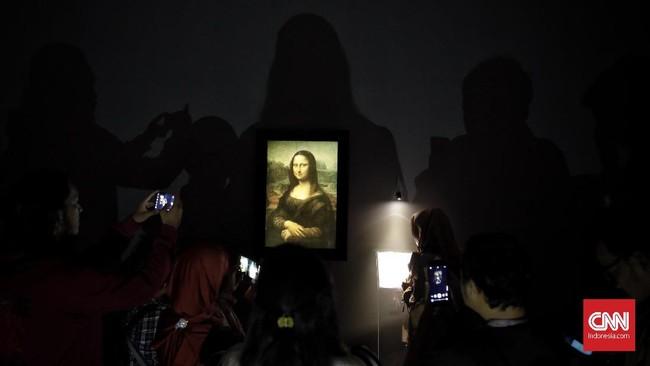 Pengunjung mengabadikan reproduksi lukisan karya Leonardo da Vinci berjudul Mona Lisa dengan gawai di pameran bertajuk Leonardo Opera Omnia. (CNN Indonesia/Adhi Wicaksono)