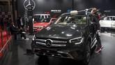 Seorang wanita menggunakan masker membersihkan mobil displaymerek Mercedes-Benz. (Photo by Money SHARMA / AFP)