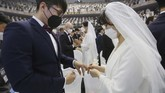 Ribuan pasangan sah menjadi suami-istri dalam pernikahan massal Gereja Unifikasi Korea, Gapyeong, Korea Selatan, Jumat (7/2). Sebagian pasangan di antaranya mengucap janji suci sembari mengenakan masker untuk mencegah penyebaran virus corona Wuhan (2019-nCoV). (AP Photo/Ahn Young-joon)