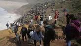 Pengunjung melihat ajang Nazare Tow Surfing Challenge di Praia do Norte, Portugal, pada Selasa (11/2). (AP Photo/Armando Franca)