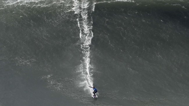 Peselancar Kai Lenny dari Hawaii yang berlaga dalam ajang Nazare Tow Surfing Challenge di Praia do Norte, Portugal, pada Selasa (11/2). (AP Photo/Armando Franca)