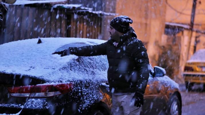 A man walks on a road while it snows in Baghdad, Iraq, Tuesday, Feb. 11, 2020. (AP Photo/Hadi Mizban)