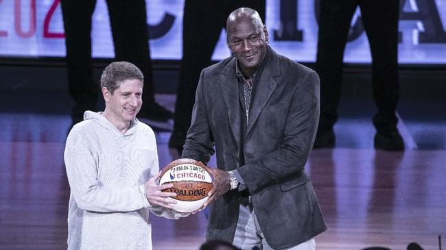 Michael Jordan menyerahkan bola kepada Presiden Chicago Bulls Michael Reinsdorf Jr. ketika Charlotte Hornets menjadi tuan rumah NBA All Star 2019. Chicago Bulls menjadi tuan rumah NBA All Star tahun ini. (Jeff Hahne/Getty Images/AFP)