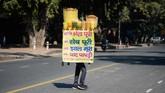 Penjual makanan ringan menyeimbangkan 'kedai' di kepalanya ketika melintasi sebuah jalan di dekat India Gate di New Delhi, Kamis (13/2). (Photo by Sajjad HUSSAIN / AFP)