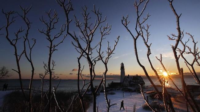 Es melapisi pepohonan di Portland Head Light, Fort Williams Park, saat seorang pengunjung tiba kawasan tersebut pada Sabtu (8/2) di Cape Elizabeth, AS. (AP Photo/Robert F. Bukaty)