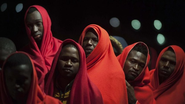 Sekelompok migran yang diselamatkan oleh otoritas maritim Spanyol tengah berdiri di atas kapal penyelamat ketika tiba di pelabuhan Malaga, Spanyol, Selasa (11/2). (AP Photo/Jesus Merida)