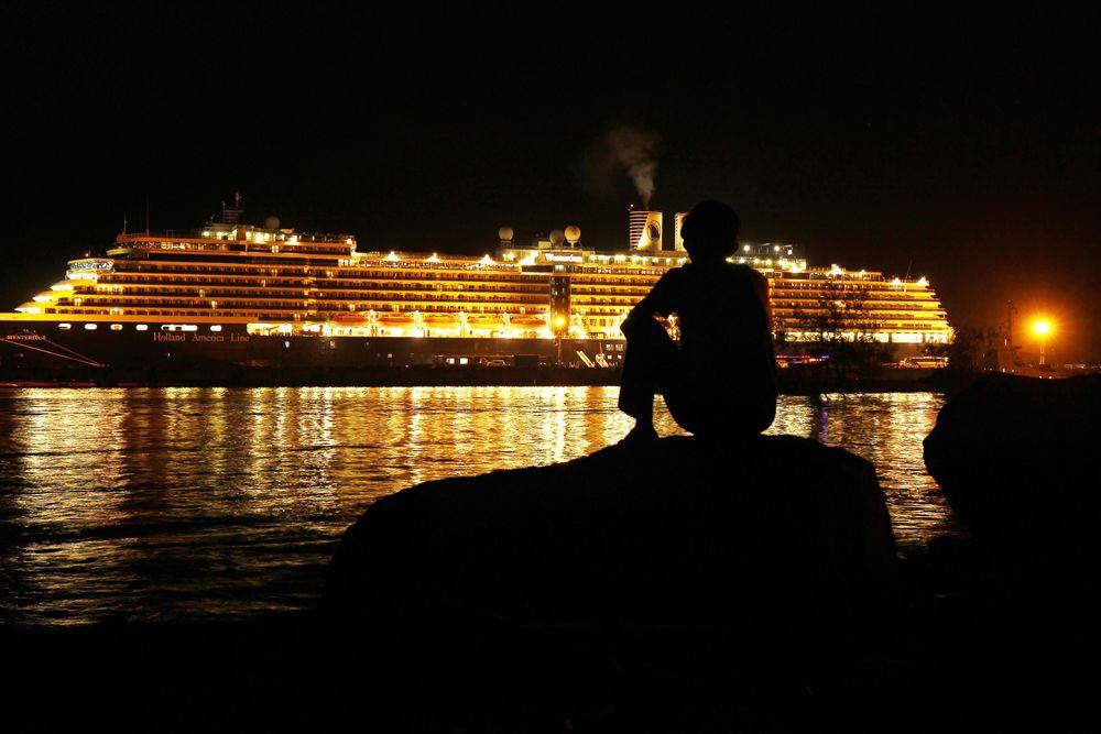 Ratusan penumpang kapal pesiar mewah MS Westerdam, bersorak saat mereka akhirnya turun dari kapal, Jumat (14/2/2020). Isu corona membuat kapal ini terombang ambing di laut selama dua minggu. Namun hari ini, kapal itu bisa berlabuh di Kamboja. (AP Photo/Heng Sinith)
