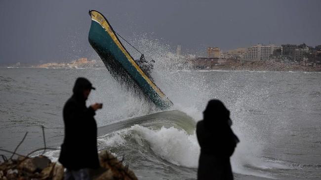 Nelayan Palestina berada di atas perahu saat ombak tinggi dan hujan tengah terjadi di Kota Gaza (Photo/Hatem Moussa)