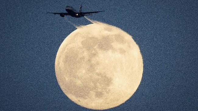 Sebuah pesawat tampak melintasi bulan saat terlihat dari Richmond Park di London, Sabtu (8/2). (Aaron Chown/PA via AP)