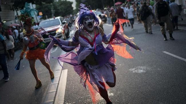Seorang peserta bersuka ria dalam tarian kostum pesta jalanan 'Banda de Ipanema' di Rio de Janeiro, Brasil, Sabtu (8/2). Ribuan orang turut merayakannya. (AP Photo/Leo Correa)