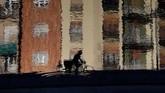 Refleksi dari seorang pengendara sepeda saat ia mengayuh pedalnya di kanal Naviglio di Milan, Italia, Selasa, (11/2) (AP Photo/Luca Bruno).