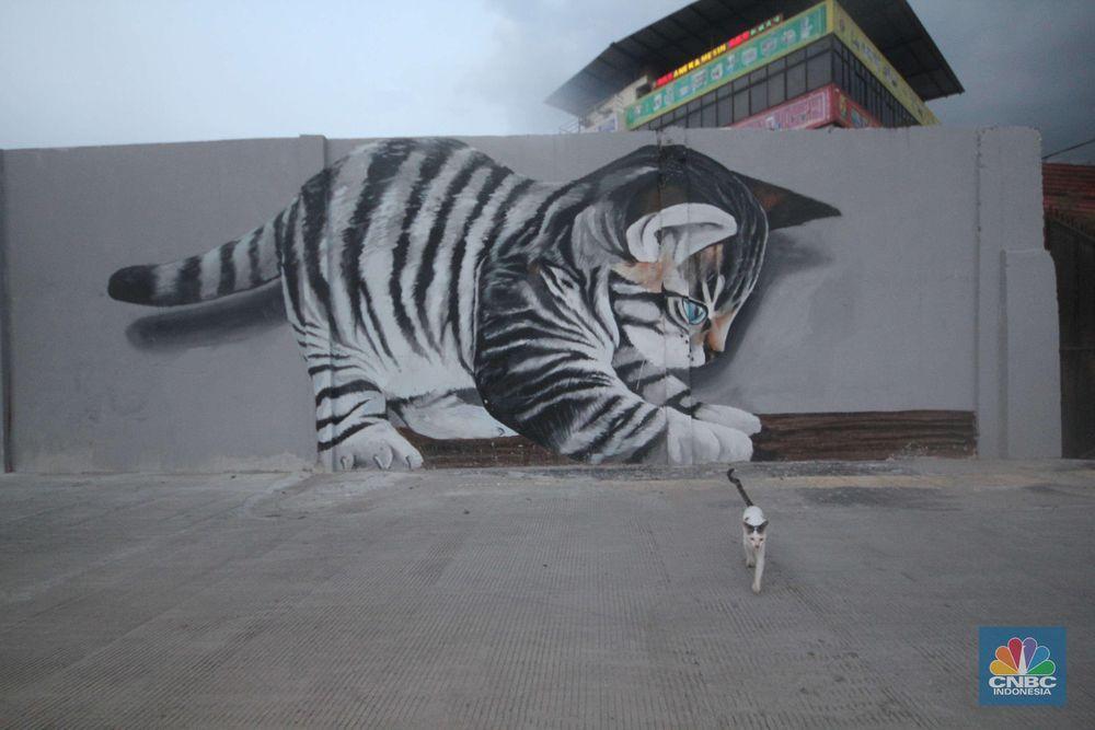 Keberadaan mural tersebut menambah estetika dalam penataan kawasan bantaran yang saat ini berfungsi sebagai jalan inspeksi. (CNBC Indonesia/Muhammad Sabki)
