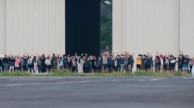 Sejumlah WNI yang dievakuasi dari Wuhan, China melambaikan tangan ke arah media saat akan senam bersama prajurit TNI pada hari ke-13 masa observasi di Hanggar Pangkalan Udara TNI AU Raden Sadjad, Ranai, Natuna, Jumat (14/2). (ANTARA FOTO/Muhammad Adimaja/foc).