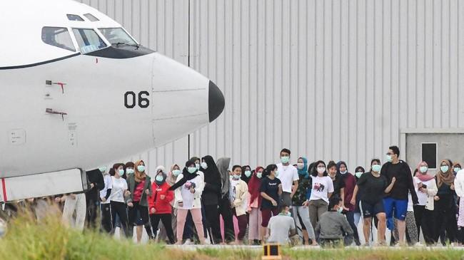 Sejumlah WNI yang dievakuasi dari Wuhan, China karena Virus Corona melakukan senam bersama prajurit TNI pada hari ke-9 masa karantina di Hanggar Pangkalan Udara TNI AU Raden Sadjad, Ranai, Natuna, Senin (10/2). (ANTARA FOTO/M Risyal Hidayat/ama).