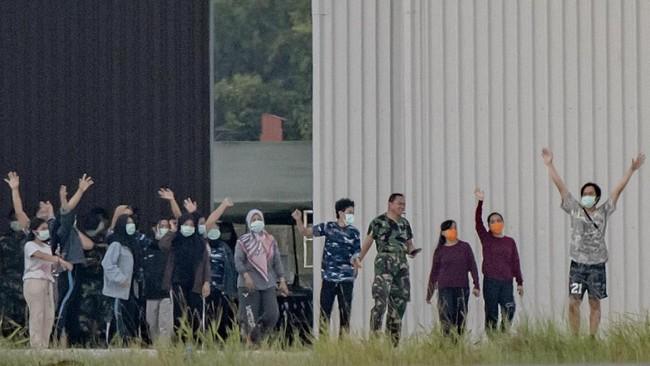 Sejumlah WNI yang dievakuasi dari Wuhan, China karena Virus Corona bersiap senam bersama prajurit TNI pada hari ke-13 masa observasi di Hanggar Pangkalan Udara TNI AU Raden Sadjad, Ranai, Natuna, Jumat (14/2). (ANTARA FOTO/Muhammad Adimaja/foc).