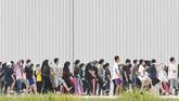 Sejumlah WNI yang dievakuasi dari Wuhan, Hubei, China karena Virus Corona senam bersama prajurit TNI pada hari ke-9 observasi di Hanggar Pangkalan Udara TNI AU Raden Sadjad, Ranai, Natuna, Senin (10/2). (ANTARA FOTO/M Risyal Hidayat/ama).