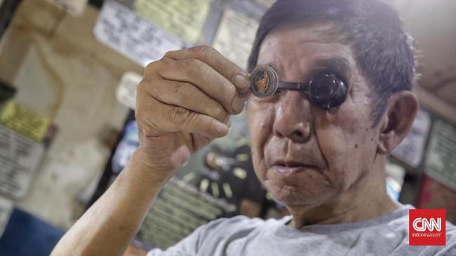 Adalah Koh Hendra Aseng, salah satu juru servis arloji yang masih bertahan di Pasar Lama Jatinegara. Pria usia 69 tahun ini meneruskan usaha sang kakak yang dimulai sejak medio 90an. Setengah berseloroh Koh Hendra mengungkapkan, merasa perlu mereparasi 'jam karet'--mengacu pada kebiasaan telat sebagian orang. (CNN Indonesia/Adhi Wicaksono)