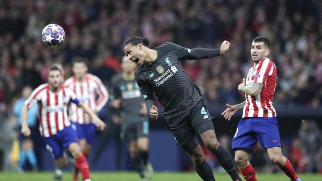 Bek Liverpool Virgil van Dijk mencoba menghalau umpan pemain Atletico Madrid Angel Correa dengan tandukannya. (AP Photo/Bernat Armangue)